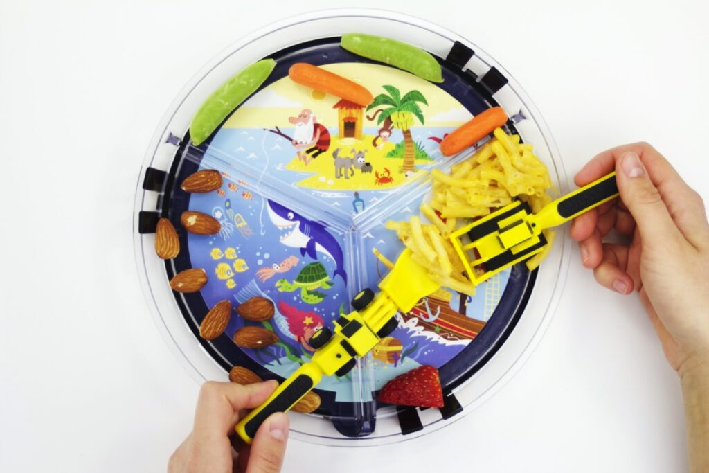 kid using construction utensils over clear round plate with seascape illustration card underneath plastic