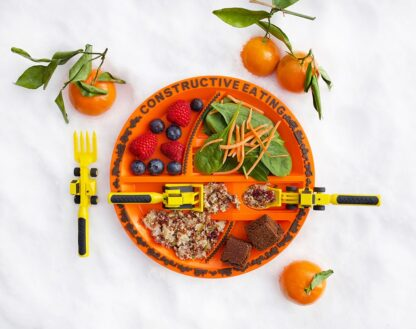 construction line orange plate and yellow utensils with food on plate and decorative oranges surrounding