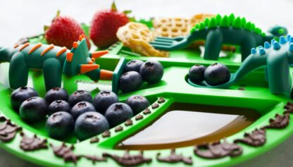 close up of dino plate full of food including waffles, strawberries, and blueberries
