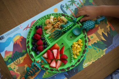 childs hand using dino fork to scoop up pasta on round green dino plate on top of illustrated dinosaur scene placemat